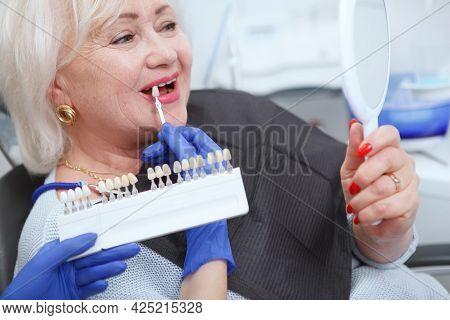 Cropped Close Up Of A Senior Woman Choosing Teeth Whitening Shade At Dental Clinic