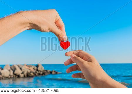 The Man's Hand Holds A Red Heart Next To The Girl's Hand Against The Sea Coast Background With A Blu