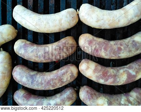 Tasty Delicious Sausages Are Cooked On Coals. Summer Picnic Concept. Grilled Sausages Roasting On Bb