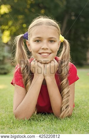Little Girl Cute Ponytails Hairstyle Relaxing On Green Grass, Summer Camp Concept