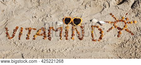 Inscription Vitamin D With Shape Of Sun Made Of Amber Stones And Sunglasses On Sand At Beach. Preven