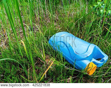 A Blue Plastic Canister In A Junkyard In The Green Grass. Container For Chemicals. Yellow Cover. Aut