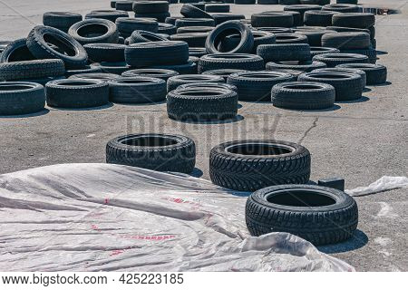 Lots Of Old Car Tires Piled Up On The Race Track. Car Tires Assembled To Create Safety Fencing On Th