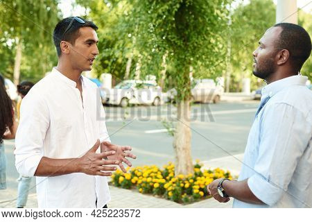 Happy Two Multiracial Male Best Friends Talking While Standing In The Street, African Guy Talking To