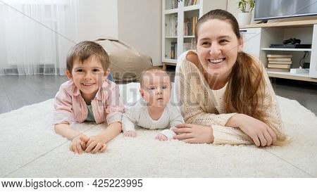 Happy Smiling Mother With Baby And Older Son Lying On Soft Carpet At Living Room. Parenting, Childre