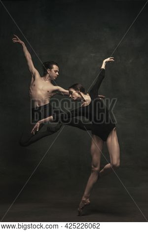 Beautiful Graceful Woman And Man, Ballet Dancers In Art Performance Dancing Isolated Over Dark Backg
