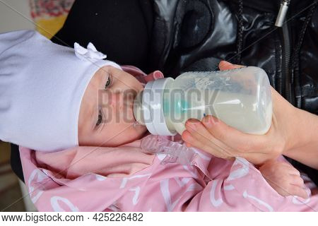 Infant Girl Sucks Milk With A Baby Bottle On Mother's Hands