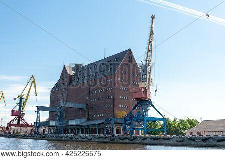 A Port Crane Near A Building In Kaliningrad.