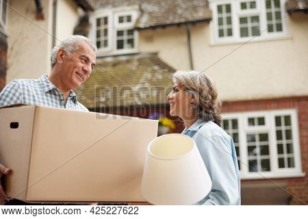 Mature Couple Carrying Boxes On Moving Day In Front Of Dream Home