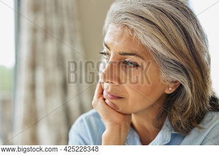Head And Shoulders Shot Of Thoughtful Mature Woman Looking Out Of Window At Home