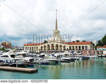 Russia, Sochi 06.06.2021. Many Yachts Moored In The Sea Against The Background Of The Sochi Seaport