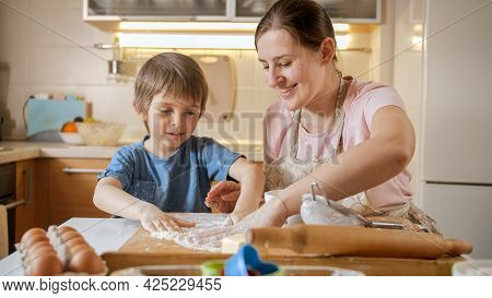 Smiling Mother With Little Son Powdering Wooden Board With Flour For Rolling Biscuits Dough. Childre