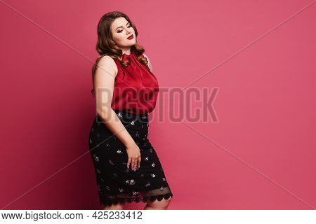 Young Plus-size Model Girl In Red Satin Blouse And Skirt Posing Over Pink Background. Pensive Chubby
