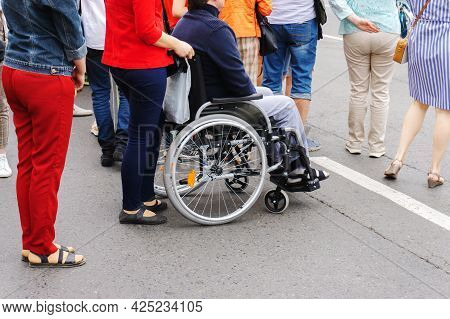 Man With Disabilities In A Wheelchair On A Street In The City. Life Of A Disabled Person In Society.
