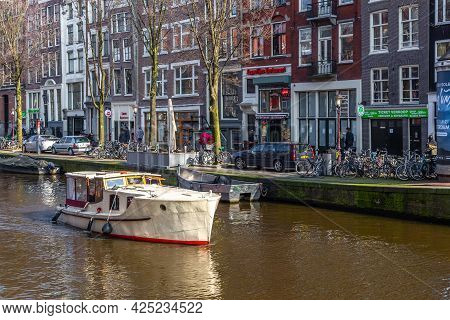 Amsterdam, Netherlands -12 March 2016: Boats On The Amstel Canal And People Walking Around. Bridge O