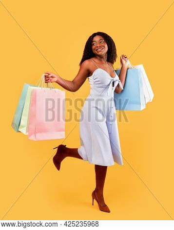 Beautiful African American Woman Holding Shopper Bags, Running And Looking Aside On Orange Backgroun