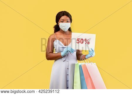 Black Lady In Medical Mask And Rubber Gloves Holding Shopping Bags And Fifty Percent Off Sign, Offer
