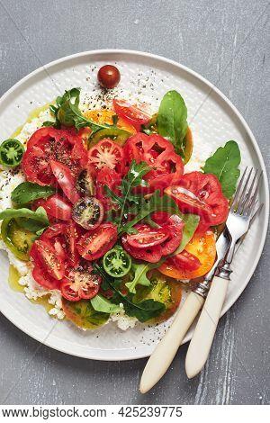 Tomato Salad With Arugula And Ricotta Cheese.