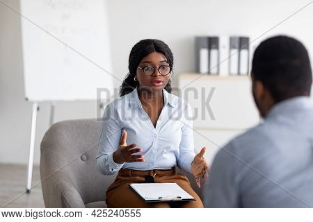 Psychological Counseling. Professional Female Psychotherapist Having Session With Young Black Guy At