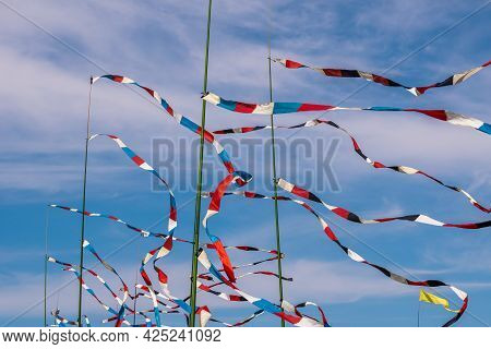 Russia. Kronstadt. June 6, 2021. Multicolored Flags On Flagpoles Flutter In The Wind Against The Blu