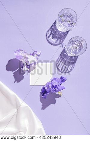 Two Glasse With Water And Card Note With Iris Flowers On Pastel Lilac Background With White Silk Clo