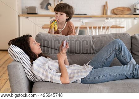 Calm Peaceful Mom Or Nanny Lying On Sofa With Mobile Phone Distracted From Noisy Loud Son Drawing At