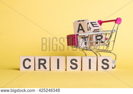 A Cart With Wooden Cubes In It And The Word Crisis Built Of Cubes On A Yellow Background. The Concep