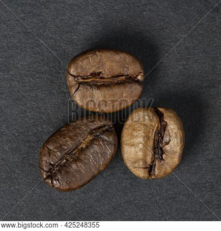 Three Beans Of High Quality Roasted Coffee On A Dark Background Close-up, Macro Photography, Top Vie