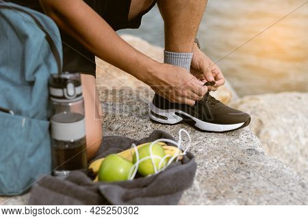 Close Up Man Tying Running Shoes Outdoor With Green Apple, Water Bottle. Male Preparing For A Run Ex