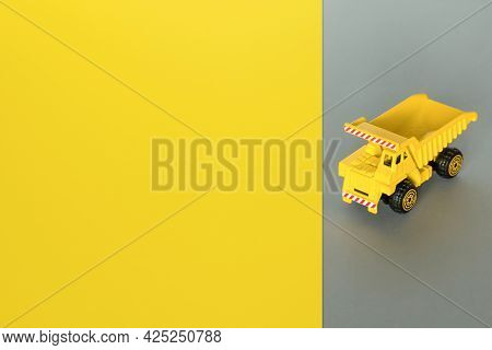 Dump Truck Service. Yellow Cargo Truck On Yellow Grey Background. Cargo Transportation, Delivery Ser