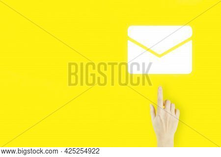 Contact Us Concept. Young Woman's Hand Finger Pointing With Hologram Email Sign On Yellow Background