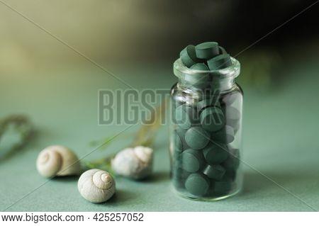 Spirulina Pills In Glass Bottle, Sea Shells On Green Background. Antioxidant Nutrition. Bio-energy,