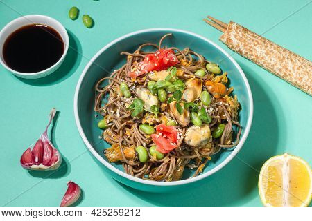 Buckwheat Soba Noodles With Vegetables And Mussels In A Blue Bowl. Close-up On A Blue Background, Wi