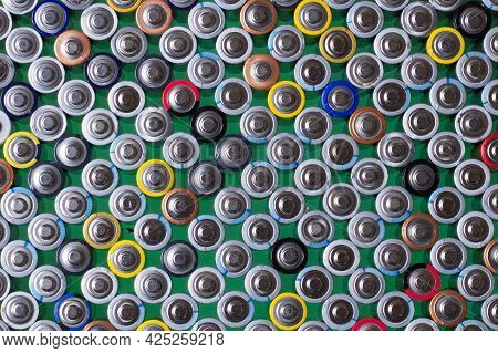 Several Alkaline Batteries On Top Of Each Other On A Green Background
