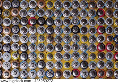 Alkaline Batteries On Top Of Each Other On A Yellow Background