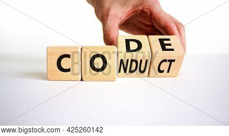 Code Of Conduct Symbol. Businessman Turns The Wooden Cube And Changes The Word Code To Conduct. Beau