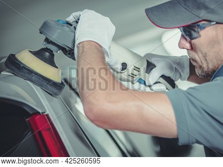 Caucasian Collision Center Worker In His 30s Polishing Car Body. Close Up Photo. Vehicle Body Repair