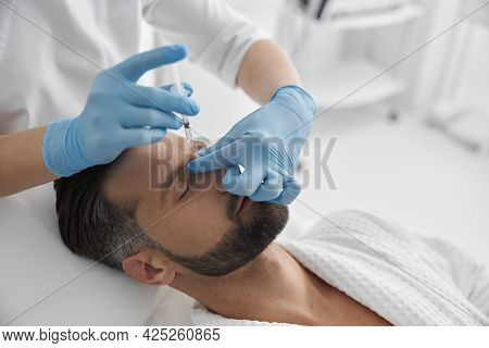 Attractive Middle Aged Man Undergoes Nasal Bridge Filler Procedure In Cosmetology Clinic