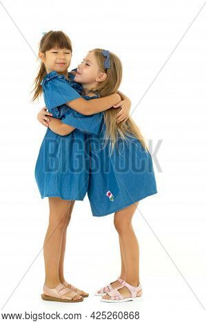Two Happy Girls Hugging Each Other. Adorable Girls Dressed In The Same Dresses Having Fun Together O