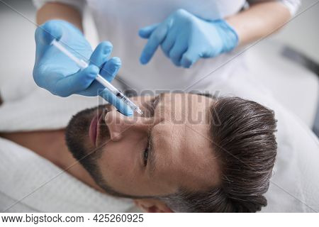 Man Grimaces Of Pain While Cosmetologist Does Injection Of Lifting Filler In His Nasal Bridge In Cli