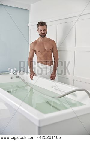 Athletic Man With Bare Chest Stands By Modern Hydro Massage Tub In Clinic