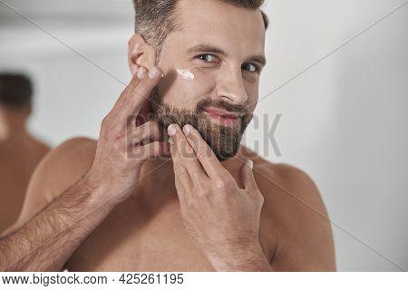 Happy Man With Stylish Beard Applies Antiaging Cream Onto Crowl Feet On Face In Bathroom