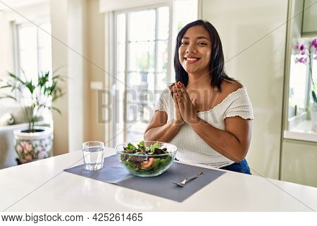 Young hispanic woman eating healthy salad at home praying with hands together asking for forgiveness smiling confident.