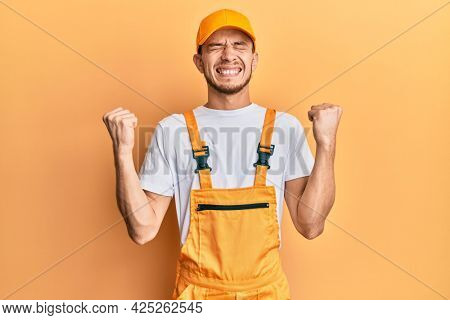 Hispanic young man wearing handyman uniform very happy and excited doing winner gesture with arms raised, smiling and screaming for success. celebration concept.