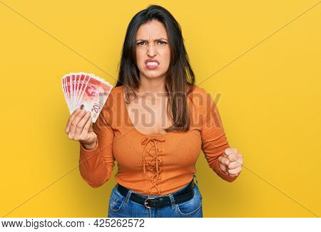 Beautiful hispanic woman holding 20 israel shekels banknotes annoyed and frustrated shouting with anger, yelling crazy with anger and hand raised