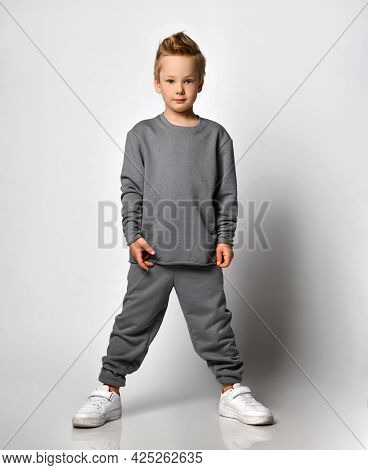 Stylish Brunet Boy Child In A Sports Sweatshirt With A Hood And Pants Stands With A Hood Over His He