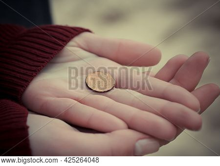 Old Coin In The Palms. The Woman Holds The Last Money In Her Hands. Poverty And Misery Concept. Bank