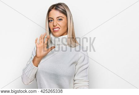 Beautiful blonde woman wearing casual turtleneck sweater disgusted expression, displeased and fearful doing disgust face because aversion reaction. with hands raised