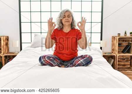 Middle age woman with grey hair sitting on the bed at home relax and smiling with eyes closed doing meditation gesture with fingers. yoga concept.