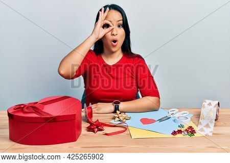 Beautiful hispanic woman with nose piercing doing handcraft creative decoration doing ok gesture shocked with surprised face, eye looking through fingers. unbelieving expression.